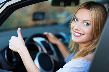 Smiling Young Woman Sitting in a Car